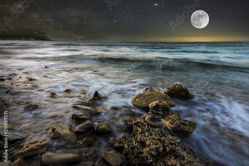 sea waves on the stone beach at night, starry sky and a full moon on the background, Zakynthos, Greece