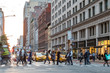 Fast paced street scene with people walking across a busy intersection on Broadway in Manhattan New York City