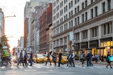 Fototapeta Nowy York - Fast paced street scene with people walking across a busy intersection on Broadway in Manhattan New York City