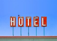 Red Hotel Sign On Top Of Old Motel Isolated On Blue Sky Background With Birds