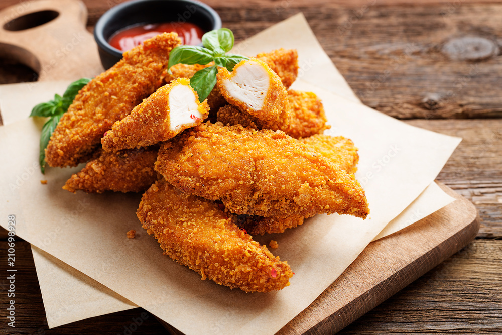 Fototapeta Delicious crispy fried breaded chicken breast strips with ketchup.