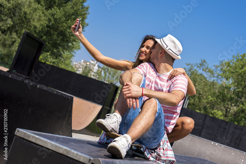 Foto op Aluminium Voetbal Happy young couple having fun in the skate park