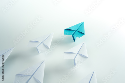Tela Business leadership concept with blue paper plane leading among white