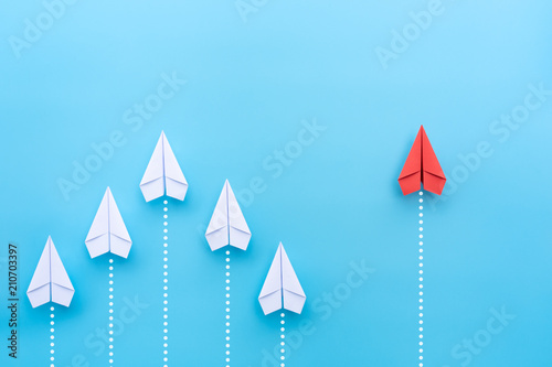 Obraz Group of paper plane in one direction and with one individual pointing in the different way on blue background. Business for innovative solution concept. - fototapety do salonu