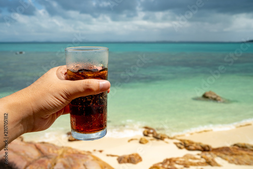 He hold Ice Soda glass a summer drink on the beach paradise, copy space of the sea Wallpaper Mural