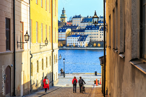 Foto op Aluminium Stockholm Tourists walking on cobble streets in Riddarholmen is part of Gamla stan is old town of Stockholm city, Sweden. Facades of medieval houses and exterior of historic buildings on shore of Baltic sea.