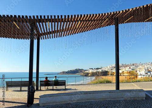 Photo Dos turistas de edad avanzada sentados en un banco en la playa de Albufeira, uno de los más visitados por el turismo europeo