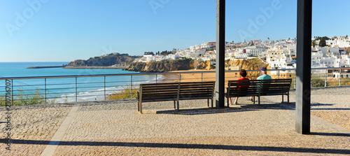 Photo Dos turistas mayores sentados en un banco en la playa de Albufeira, una de las más visitadas por los turistas europeos