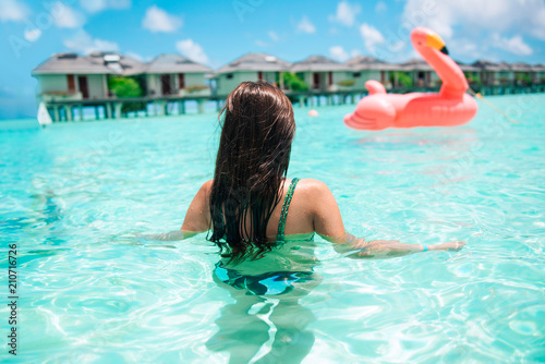 Obraz na plátne Beautiful young woman posing in sensual swimsuit sitting on a flamingo