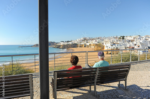 Two elderly tourists sitting on a bench in the beach of Albufeira, one of the most visited by European tourism Canvas Print