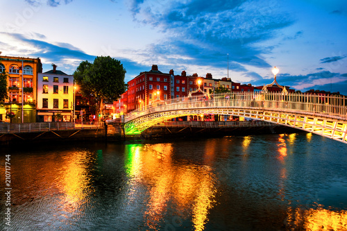 Night view of famous illuminated Ha Penny Bridge in Dublin, Ireland at sunset Wallpaper Mural