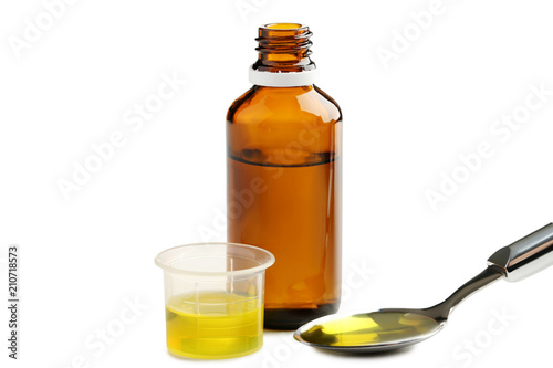 Fotografia  Bottle, measuring plastic cup and spoon with medical syrup on white background