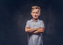 Cute Little Boy Dressed In A White T-shirt Standing With Crossed Arms In A Studio. Isolated On Dark Textured Background.