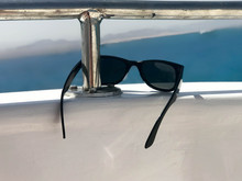 Black Plastic Sunglasses Hang On An Iron Railing On A Yacht, A Cruise Liner Against The Blue Sea And Mountains.