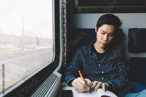Man writing a note on the train