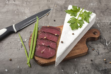 Jerky Meat On A Wooden, Cutting Board And Green Onions. Soft Cheese With White Mold
