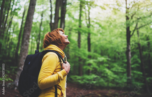 smiling tourist traveler with backpack into road at summer green forest, girl hiker in yellow hoody looking and enjoying the breath of fresh air in trip, relax holiday concept, blurred background