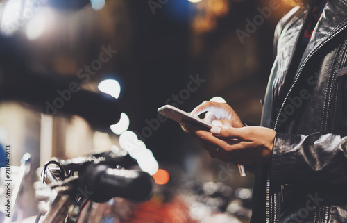 girl in black leather jacket using in hands screen smartphone on