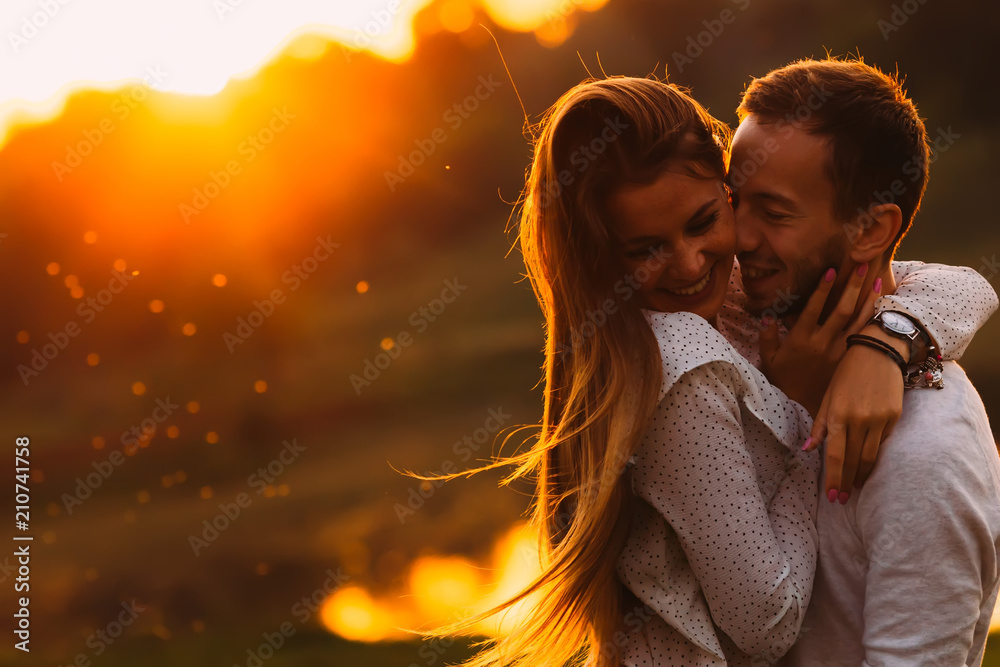 Fototapety, obrazy: passionate hug of a couple in love on the shore of an evening la