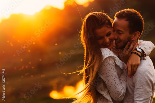 Obraz sensual hugs of a guy and his girlfriend against the background - fototapety do salonu