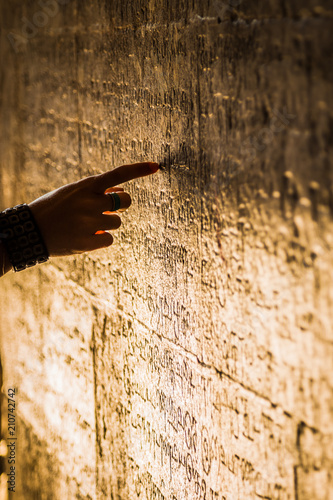 Woman hand pointing ancient script on a wall carving at an Indian temple