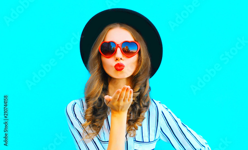 Valokuvatapetti Cool girl with red lips is sends an air kiss in a sunglasses shape of heart over