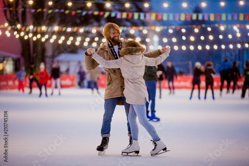 Theme ice skating rink and loving couple. meeting young, stylish people ride by hand in crowd on city skating rink lit by light bulbs and lights. Ice skating in winter for Christmas on ice arena