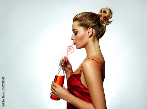 A beautiful tanned girl in a red silk dress and with red lipstick drinks a red drink from a glass bottle through a red straw.