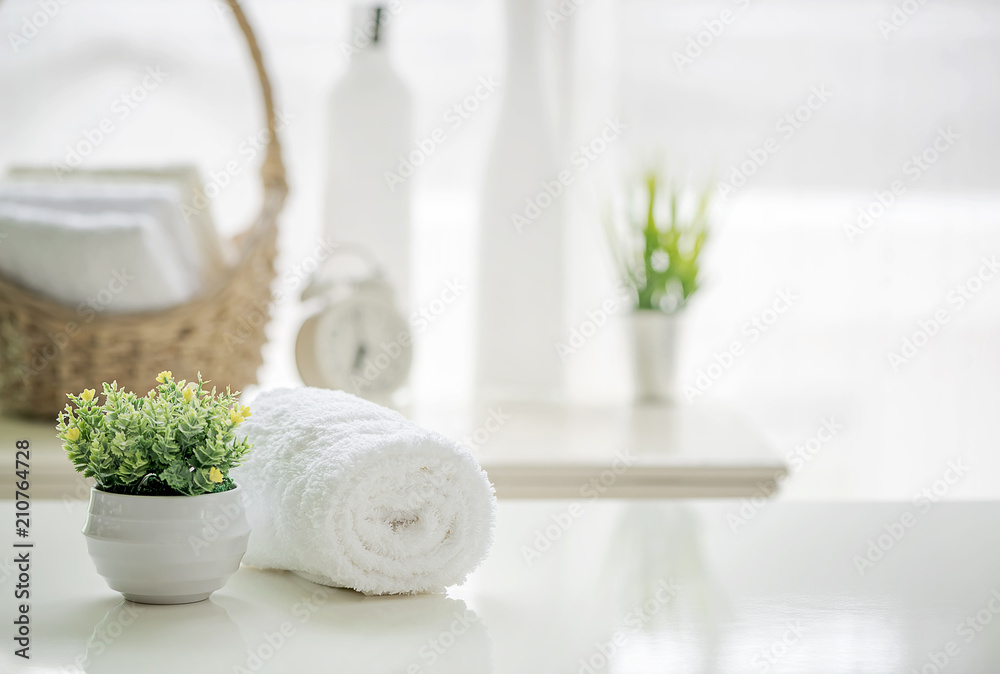 Fototapety, obrazy: Roll up of white towels on white table with copy space on blurred living room background