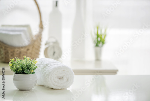 fototapeta na ścianę Roll up of white towels on white table with copy space on blurred living room background
