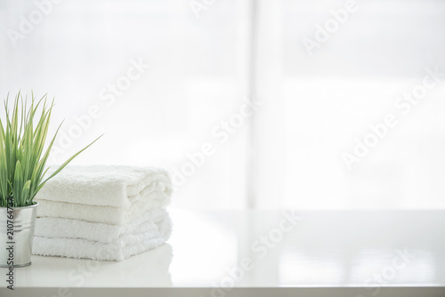 Towels and houseplant on white table with copy space