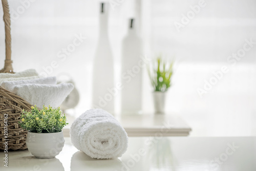 White towels on white table with copy space on blurred bathroom background.