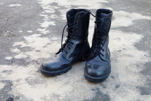 Man Boot Black Military Shoes Isolated. Top View. Black Combat Boots On Gray Concrete Background