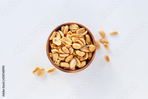 Fotografía Roasted salted peanuts in wooden bowl on white background.