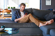 Wide Shot Of An Attractive Caucasian Man Sitting On A Generous Sofa In A Modern Home, While Texting On His Latest Mobile Phone With His Feet Up On The Couch And Relaxing.