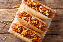 Authentic Chili Hot Dog With Cheddar Cheese, Onion And Spicy Sauce Close-up On Paper. Horizontal Top View