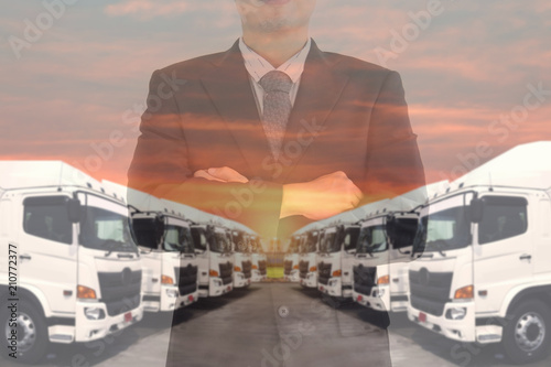 Double exposure of business man with Haulage trucking fleet as in trucking manager Canvas Print