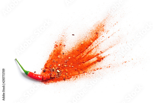 Photo  Chili powder and flakes burst out from red chili pepper