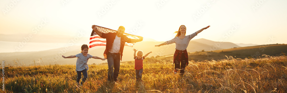 Fototapety, obrazy: happy family with flag of america USA at sunset outdoors.