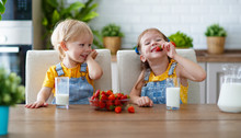 Happy Children Brother And Sister Eating Strawberries With Milk.