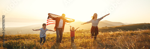 Obraz happy family with flag of america USA at sunset outdoors. - fototapety do salonu