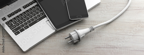 Computer, laptop, smartphone and power plug on wooden background Fototapete