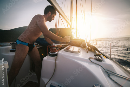 Poster Zeilen Sailor pulling rope on sailboat on the sunset sea