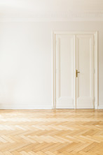 Copy Space On White Wall Next To Door In Empty Living Room Interior With Wooden Floor. Real Photo