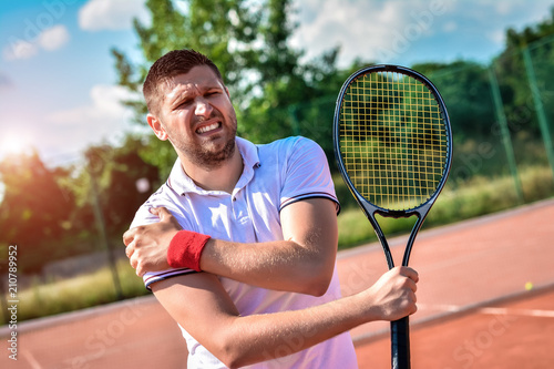 Fototapeta Shot of a tennis player with a shoulder injury on a clay court obraz
