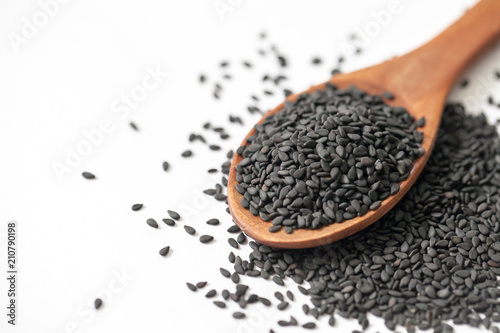 black sesame seeds in wooden spoon on white background Canvas Print