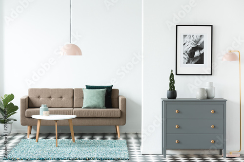 Fotografie, Obraz  Brown sofa with green cushions standing in white open space living room interior