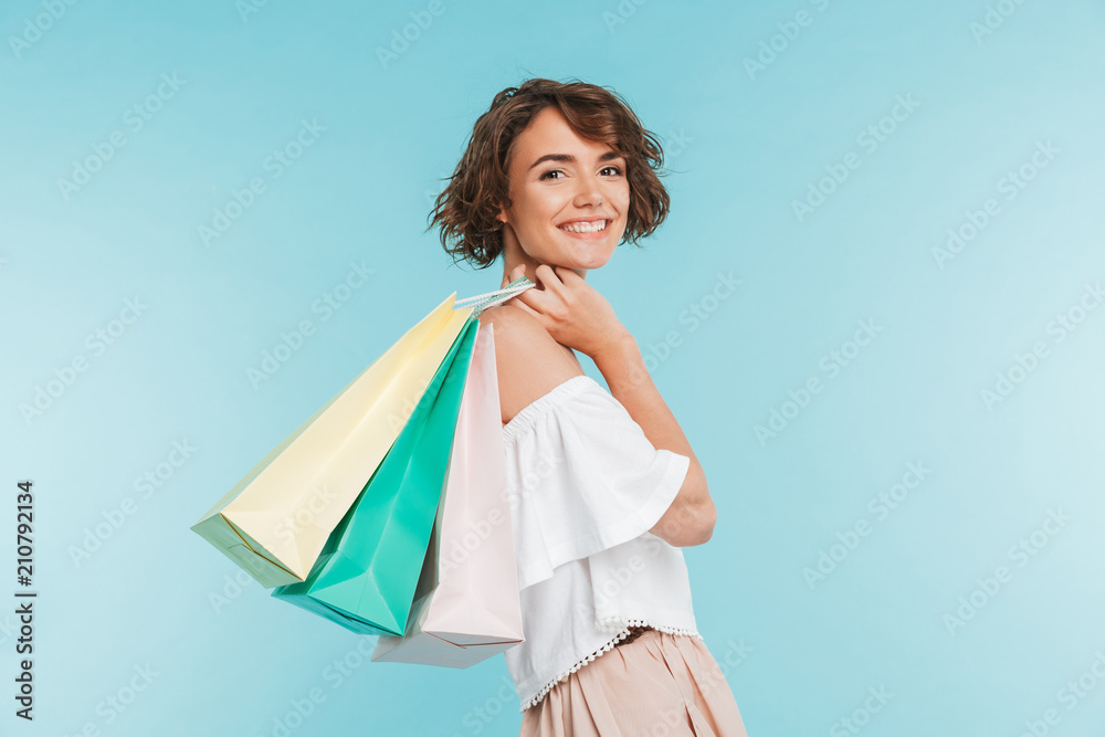 Fototapeta Portrait of a smiling young woman holding shopping bags