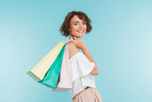 Portrait Of A Smiling Young Woman Holding Shopping Bags