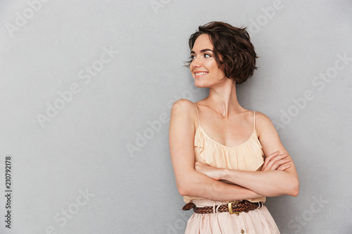 Portrait of a smiling young woman standing with arms folded Canvas Print